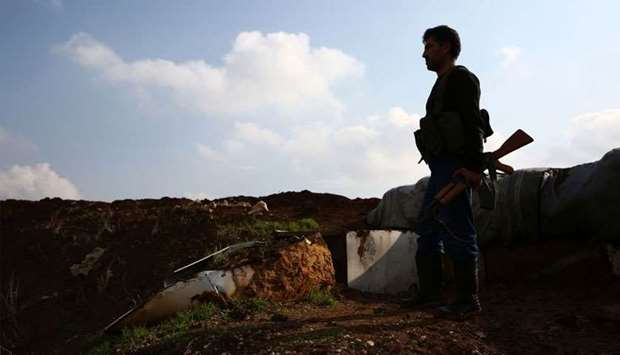 A Turkish-backed Syrian fighter holds a position in the village of Tal Malid