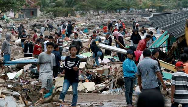 Rescuers and residents look for survivors along the coast in South Lampung on South Sumatra  after t