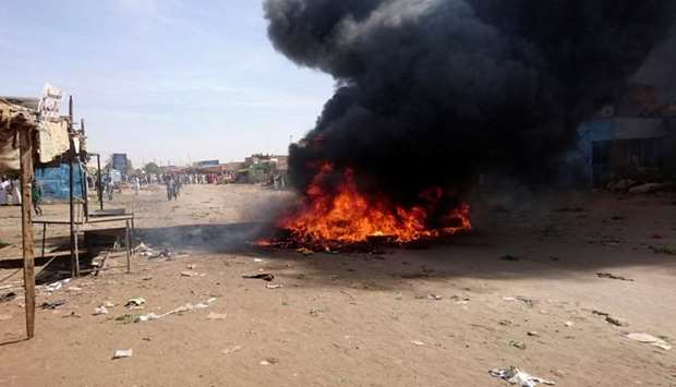 A bonfire is lit along the street during protests against price increases in Atbara, Nile River stat