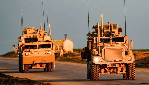 US Marine Corps tactical vehicles are seen driving along a road near the town of Tal Baydar in the