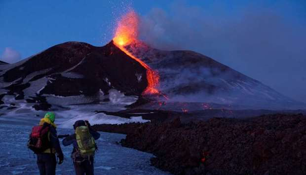 Volcano guides stand in front of Italy's Mount Etna,