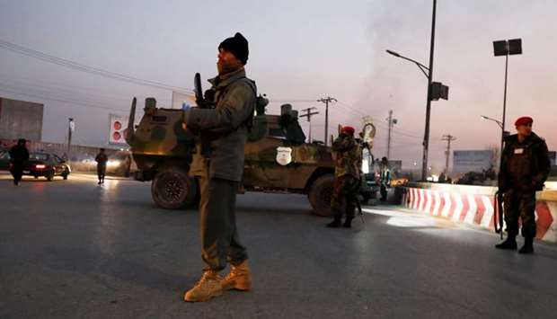 Afghan security forces stand guard at the site of an attack in Kabul, Afghanistan