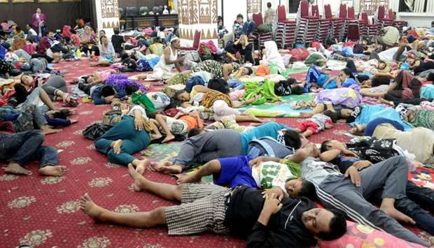 Residents, who lived at coast of Bandar Lampung, rest at government building after they evacuated fo