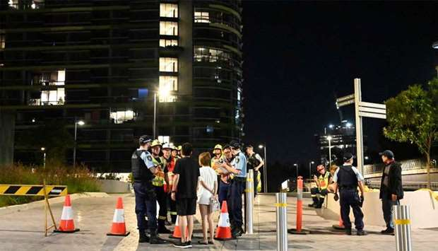 Police check the unit numbers of the residents after an inspection of the Opal Tower by firefighters