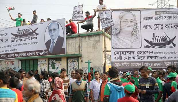 People stand on a rooftop as they join in a campaign of the Bangladesh Awami League
