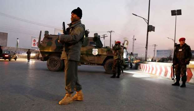 Afghan security forces stand guard at the site of an attack in Kabul