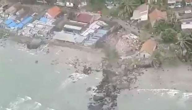Debris surround buildings along a shore after a tsunami hit Kalianda, Lampung province, Indonesia