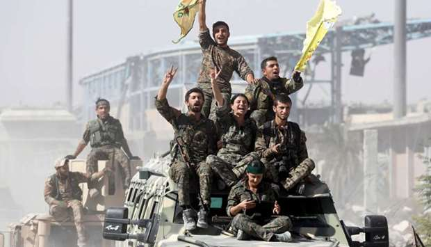 Kurdish-led militiamen ride atop military vehicles as they celebrate victory over Islamic State in R