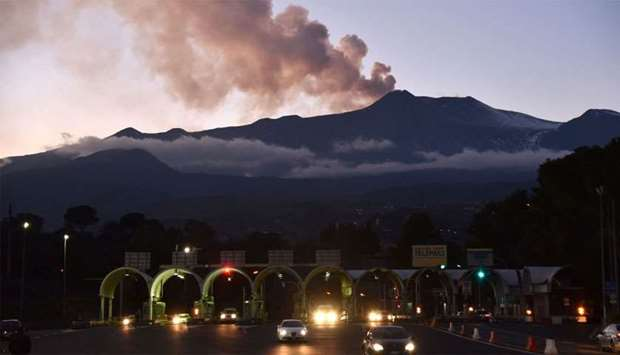 Smoke rises from Mount Etna as seen at sunset from the city of Giarre, Catania, as motorists go thro