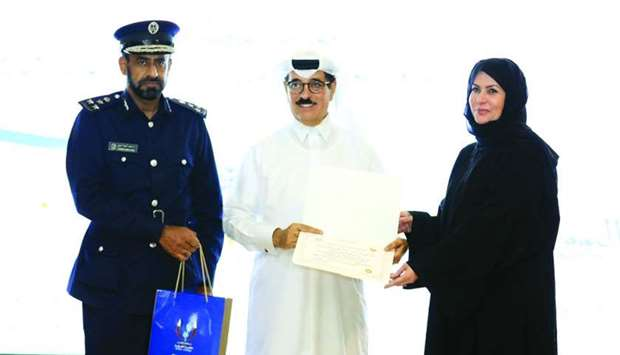 HE al-Kuwari presents a certificate as al-Marri looks on.