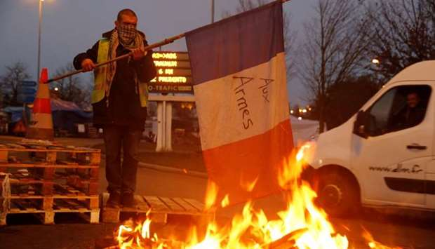 A protester wearing a yellow vest holds a flag near burning debris at the approach to the A2 Paris-B