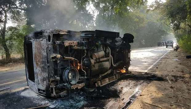 An upturned and smouldering vehicle is seen following mob violence at Chingravati village in Uttar P