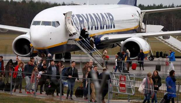 People walk on the tarmac as they leave a Ryanair aircraft at the airport in Modlin near Warsaw, Pol