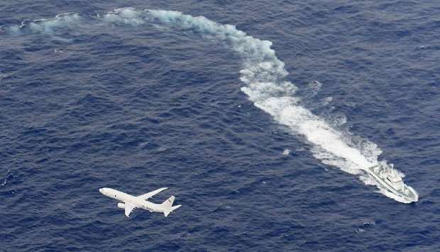 A Japan Coast Guard patrol vessel and US Navy airplane conduct search and rescue operation at the ar