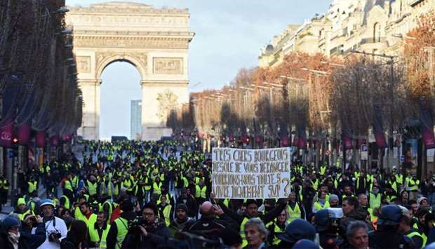 "A ""yellow vest"" (gilet jaune) protestor holds a sign reading ""Dear bourgeois we are deeply sorry to"