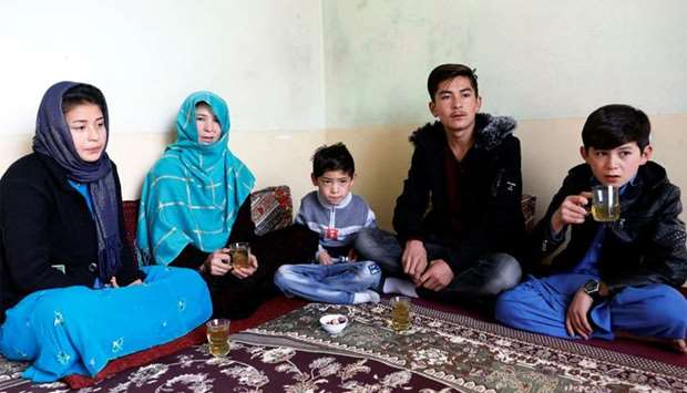 Murtaza Ahmadi, 7, (C) an Afghan Lionel Messi fan, sits with his family at their house in Kabul