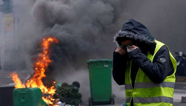 A protester wearing a yellow vest stands next to burning trash bins in a street during a national da