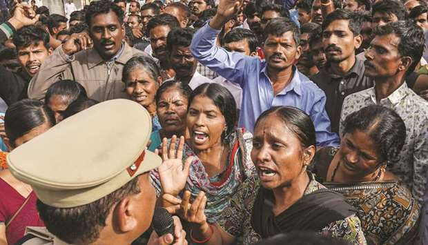 Demonstrators argue with a police officer during a protest yesterday in Shadnagar, on the outskirts