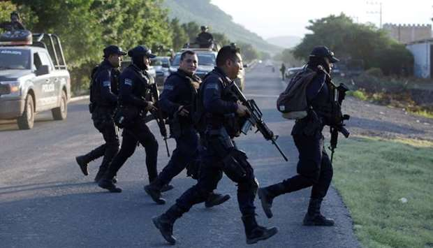 Police officers patrol at a road after fellow police officers were killed during an ambush by suspec