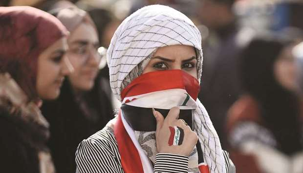 An Iraqi student covers her face with a national flag as she takes part in an anti-government demons
