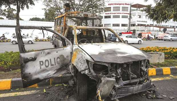 A burnt-out police van is seen outside the cardiac hospital in Lahore yesterday.