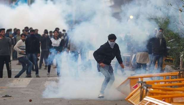 Protesters run for cover amid tear gas fired by police during a protest against the Citizenship Amen