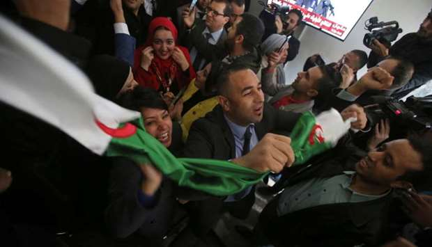 Supporters react at the campaign headquarters of Abdelmadjid Tebboune after he was announced as the