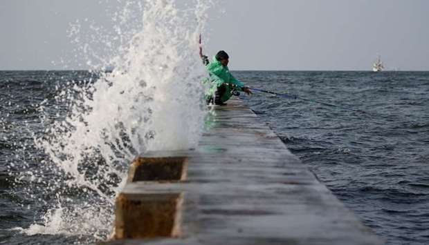 A man sits as he fishes at the sea wall built in an area affected by land subsidence and rising sea