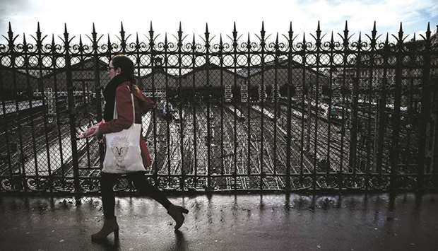 A woman crosses a bridge over empty tracks leading to the Saint-Lazare railway station in Paris.