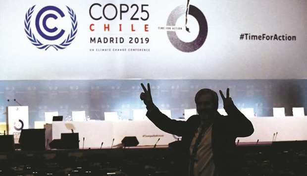 A man gestures in front of empty chairs, on the last day of the UN climate Change Conference COP25 a