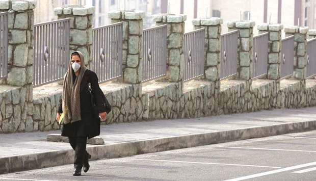 An Iranian woman, wearing a breathing mask walks down a street as a blanket of smog covers the city