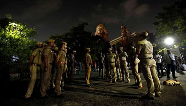 Police stand guard inside a Madras university compound during a protest by the university students a