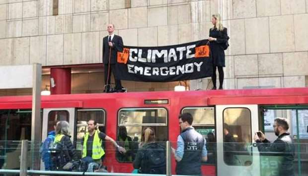 Climate protesters with the Extinction Rebellion group climb on top of a train at London's Canary Wh
