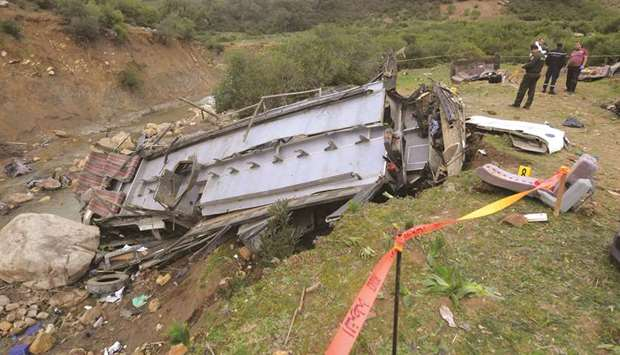 Security forces check the debris of a bus that plunged over a cliff into a ravine, in Ain Snoussi in