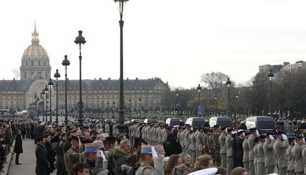 Soldiers salute the funeral convoy on Alexandre III Bridge in front of the Invalides monument in Par