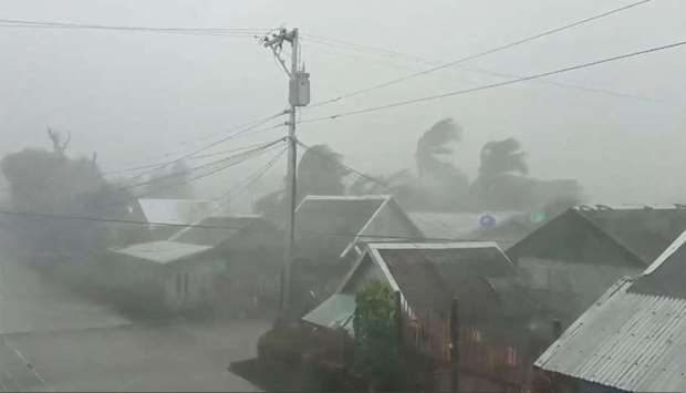Trees sway near buildings as Typhoon Kammuri, known locally as Typhoon Tisoy, makes landfall in Gama