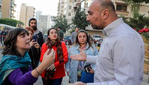 Lebanese anti-government demonstrators (L) argue with a representative of the popular movement (R),