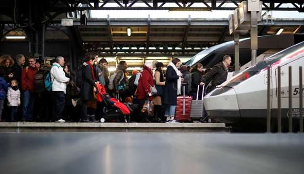 Commuters walk on a platform at Gare de l'Est train station during a strike by all unions of French