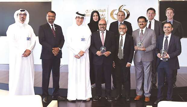 Senior Commercial Bank executives with the awards won by the bank in recognition of its leading digi