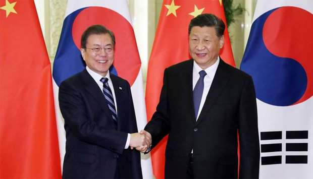 South Korea's President Moon Jae-in (L) shakes hands with China's President Xi Jinping (R)