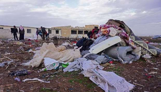 Syrians inspect the site of a Russian air strike in the village of Jubass on the outskirts of Saraqe