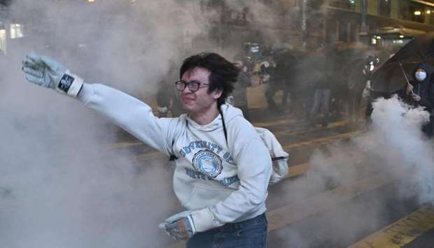 People rush into a building as police fired tear gas on a street to disperse bystanders during a pro