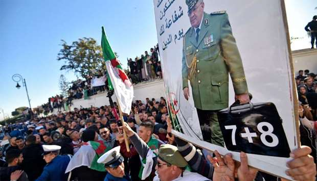 People hold up a portrait of Algeria's late military chief Lieutenant general Ahmed Gaid Salah as th