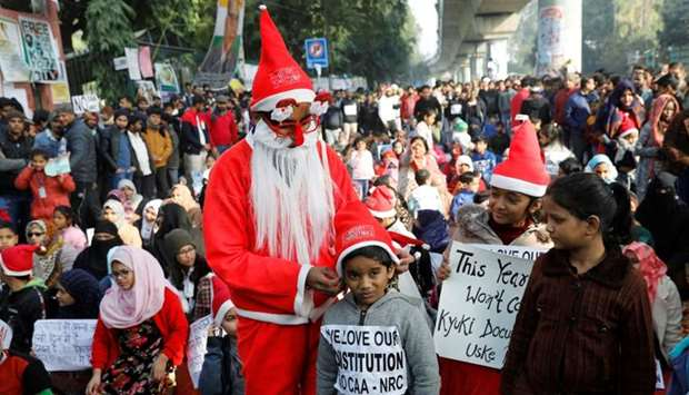 A man wearing a Santa Claus costume gives hats to kids during a protest against a new citizenship la