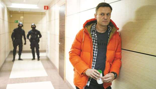 Navalny stands near law enforcement agents in a hallway of a business centre, which houses the offic