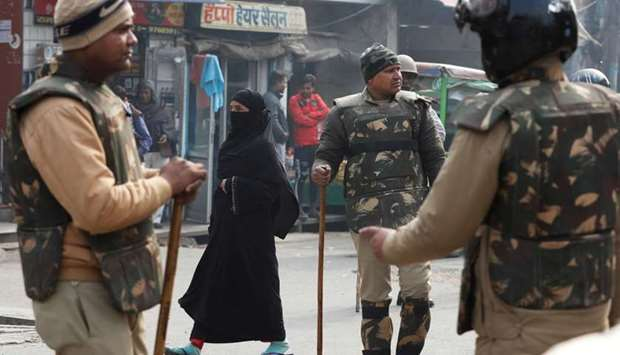 A veiled Muslim woman walks past policemen in riot gear on a street in Meerut, in the northern state