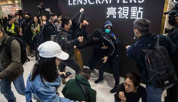 Plainclothes police officers (with batons) clash with a pro-democracy protester during a rally insid