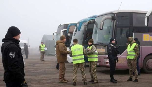 Ukrainian law enforcement officers and servicemen stand guard near buses for pro-Russian rebels befo