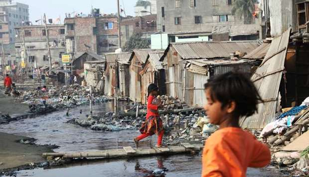 A girl, who lives in polluted environment in a slum, carries a water bottle in Dhaka, Bangladesh