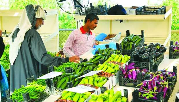 A customer selects vegetables at an outlet at a yard.